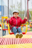 Cute kids on a chain swing carousel. Having fun Royalty Free Stock Photo