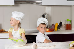Cute Kids in Chefs Attire in Kitchen. Cute Kids in Chefs Attire Baking Something to Eat in the Kitchen royalty free stock images