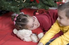 Cute kids at Christmas. In front of a Christmas tree a girl lies on her belly resting her head on a teddy bear while looking up at her big brother Stock Images