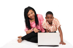 Cute kids computer fun. Two cute kids at home sitting on bed having fun on computer Royalty Free Stock Photos