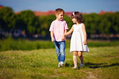 Cute kids, couple walking on summer field Royalty Free Stock Images