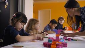 Cute kids drawing with teacher at preschool class