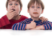Cute kids eating cookies Royalty Free Stock Images
