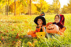 Cute kids in Halloween costumes sitting on grass Stock Image