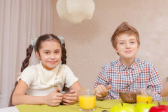 Cute kids have a meal at home Stock Photos