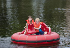 Cute kids having fun riding bumper boats on a lake stock image