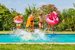 Cute kids jumping in swimming pool with swim rings royalty free stock photography