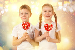 Cute kids little boy and girl with candy red lollipop in heart shape. Valentine`s day art portrait. Royalty Free Stock Image