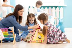 Cute kids playing with busy board in kindergarten. Children`s educational toys. Wooden game board. royalty free stock photos