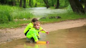 Cute Kids Playing Cars In Huge Puddle In Park stock footage