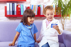 Cute kids playing doctors in office Stock Images