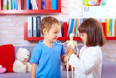 Cute kids playing in doctors with toy human skeleton Stock Photos