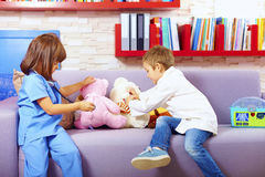 Cute kids playing doctors with toys in office Royalty Free Stock Image