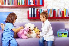 Cute kids playing doctors with toys in office Stock Photography