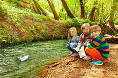 Cute kids playing with paper ships at riverside Stock Photos