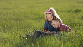 Cute kids playing on smartphones sitting on grass. stock video footage