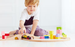 Cute kids playing with toy railway road at home. focus on train Stock Images