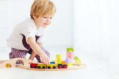 Cute kids playing with toy railway road at home. focus on train Royalty Free Stock Photography