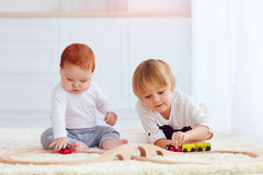 Cute kids playing with toy railway road at home Royalty Free Stock Photos