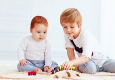 Cute kids playing with toy railway road at home Royalty Free Stock Image