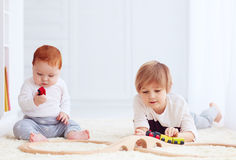 Cute kids playing with toy railway road at home Stock Photography