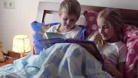 Cute kids reading book in bed. Two cute kids reading book in bed stock video footage