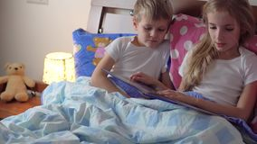 Cute kids reading book in bed. Two cute kids reading book in bed stock footage