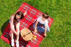 Cute kids ready for picnic in summer meadow. Top view portrait of happy boy and girl sitting on red checkered picnic blanket with hand basket Royalty Free Stock Image