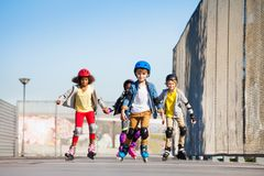 Cute kids on roller skates riding outdoors stock photos