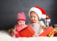 Cute kids on rug opening a Christmas present Stock Image