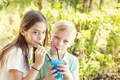 Cute kids sharing a delicious flavored ice drink together. Two cute thirsty kids sharing a delicious and refreshing flavored ice drink together on a warm summer Royalty Free Stock Image