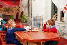 Cute kids sitting in cafe Stock Photo
