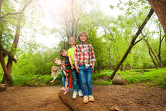 Cute kids standing on a log in the forest Royalty Free Stock Image
