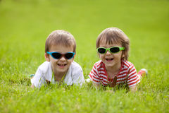 Cute kids with sunglasses, eating chocolate lollipops. At the park Royalty Free Stock Photography