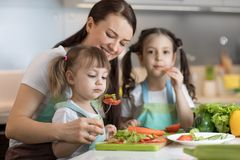 Cute kids tasting vegetables as they prepare a meal with their mother in the kitchen. Cute kids sisters tasting vegetables as they prepare a meal with their royalty free stock photo