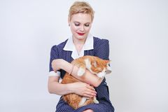 Cute kind woman with short hair in pinup polka dot dress holding her beloved pet on a white background in the Studio. plus size ad. Ult blonde girl and her royalty free stock photo