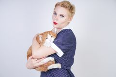 Cute kind woman with short hair in pinup polka dot dress holding her beloved pet on a white background in the Studio. plus size ad. Ult blonde girl and her stock images