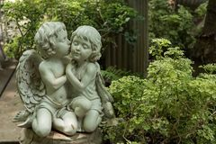 Cute kissed couple cupid in garden. Cute kissed couple cupid Statue in greenery garden Stock Photos