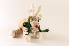 Cute knitted deer toy with green scarf. On the white background Stock Photos
