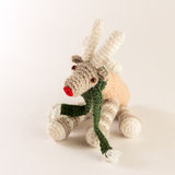 Cute knitted deer toy with green scarf. On the white background Royalty Free Stock Photo