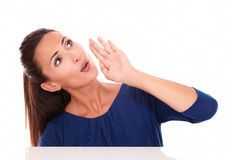 Cute lady in blue shirt looking up while speaking Royalty Free Stock Photos