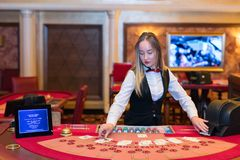 Cute lady casino dealer at Black Jack table Royalty Free Stock Photography