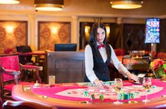 Cute lady casino dealer at Black Jack table Stock Photo