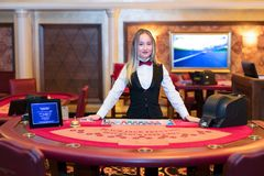 Cute lady casino dealer at Black Jack table Stock Image