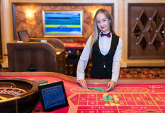 Cute lady casino dealer at Roulette table. Stock Photos