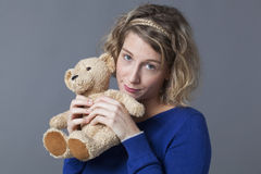 Cute lady holding up her cuddly toy remembering Stock Photos
