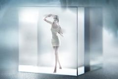 Cute lady imprisoned in a glass cube Stock Images