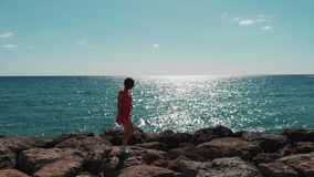 Cute lady in red dress flapping on wind walking on rocks on pier in sea with sun reflection on blue ocean water. Sunny hot day in. Cyprus coral beach with stock footage
