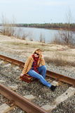 Cute Lady sitting on the rails with vintage suitcase Stock Photography