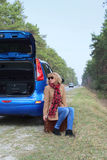 Cute Lady sitting with suitcases on the road near the blue car Stock Photos